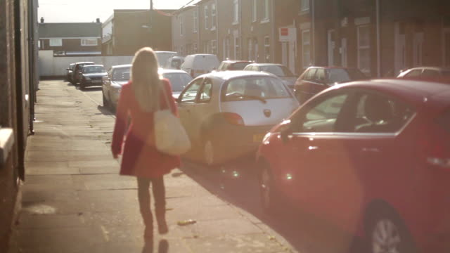 vidéos et rushes de attractive beautiful young blonde woman walks on city street on sunny day - cheveux blonds