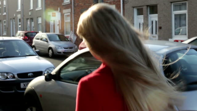 attractive beautiful young blonde woman walks on city street on sunny day