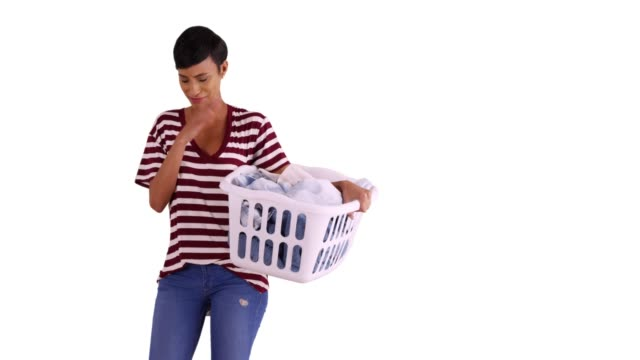 attractive black female holding basket of clean clothes and sneezing in studio - detersivo per bucato video stock e b–roll