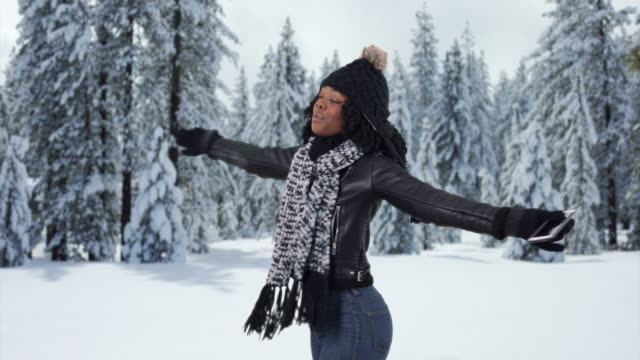 attractive black female holding her arms out and twirling in snowy forest - leather jacket stock videos & royalty-free footage