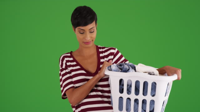 attractive black female holding laundry basket on green screen - laundry basket stock videos and b-roll footage