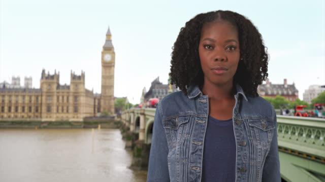vídeos de stock, filmes e b-roll de attractive black woman traveling in london stands by westminster bridge, smiling - jaqueta jeans