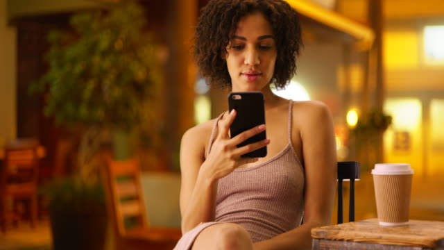 Attractive black woman watching cute cat videos on her smartphone device.  Portrait of cute woman sitting, enjoying cell phone in Havana, Cuba.