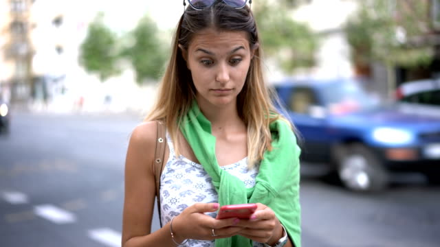 vídeos de stock, filmes e b-roll de mensagens de loira atraente em seu telefone na cidade - olhos verdes