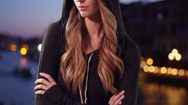 vídeos de stock e filmes b-roll de attractive blonde female wearing a hoodie outside in evening - sweatshirt