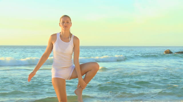 vídeos de stock, filmes e b-roll de attractive blonde woman doing yoga on a beach / cape town, western cape, south africa - pose de arvore