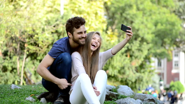 Attractive boy and girl couple taking selfie in park.