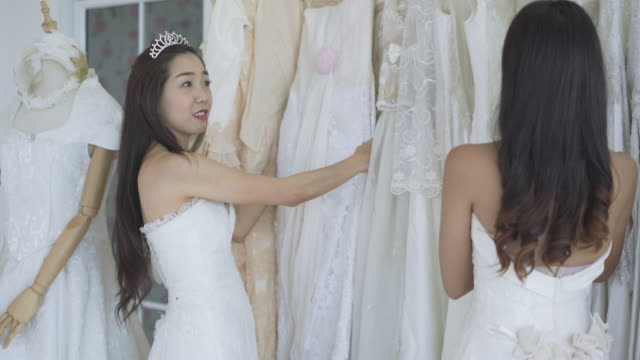 attractive bride choosing a wedding dress in the store,young beautiful bride wearing fluffy dress posing in studio room - wedding dress stock videos & royalty-free footage