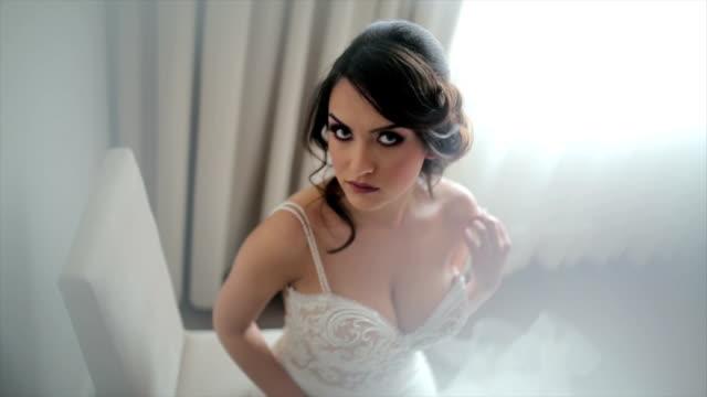 attraktive braut posiert in ihrem hochzeitskleid - weibliche brust stock-videos und b-roll-filmmaterial