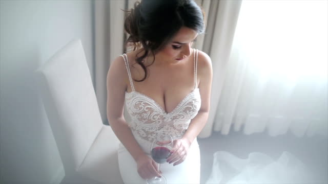 vídeos de stock e filmes b-roll de attractive bride with a glass of wine posing in her wedding dress - mulher sedutora
