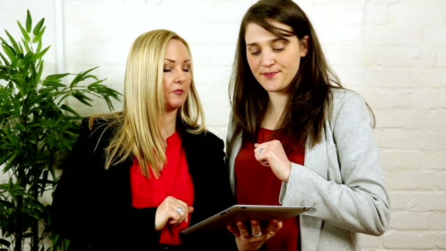 attractive british women using and demonstrating ipad tablet app - employee engagement stock videos & royalty-free footage