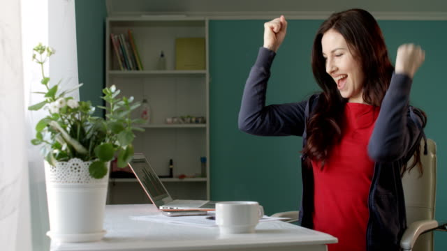 attractive brunette woman freelancer working from home computer and talking on the phone rejoicing success with sales - good news stock videos & royalty-free footage