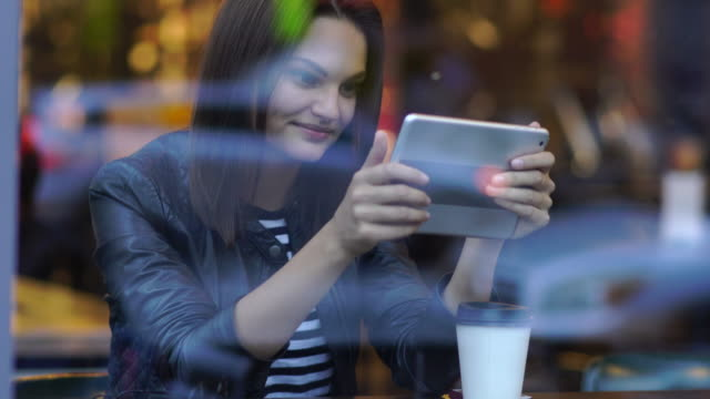 attractive brunette women reading on tablet computer in coffee shop