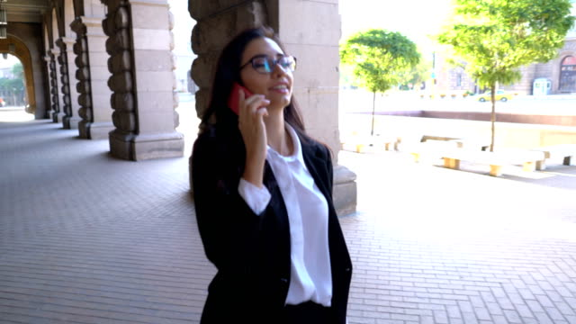 Attractive business lady talking on the telephone and walking