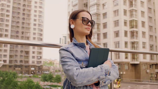 vidéos et rushes de attractive business woman stands holding a tablet feels confident - 25 29 years