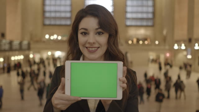 attractive business women commuting to work holding digital tablet with green screen