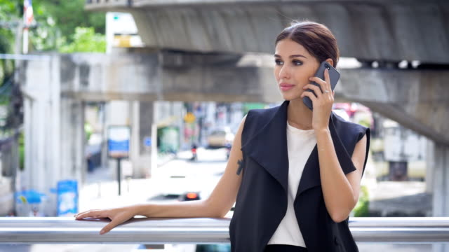 Attractive businesswoman calling on smart-phone at outdoors