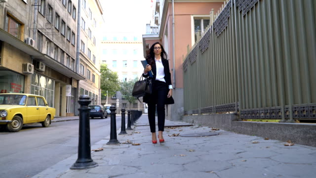 Attractive businesswoman walking on the street, holding file folder and fixing her eyeglasses