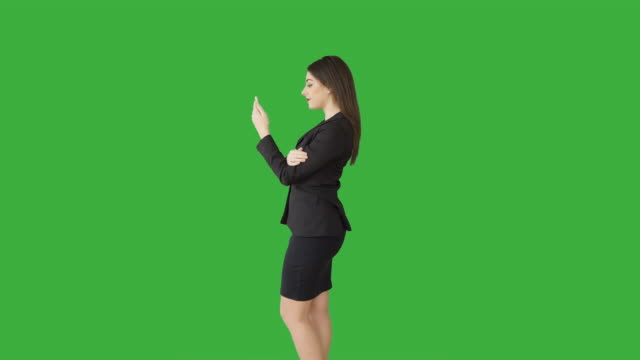 attractive caucasian brunette using phone in front of a green screen. beautiful businesswoman in businesswear standing against green backgound. - three quarter length stock videos & royalty-free footage