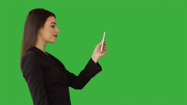 Attractive Caucasian Brunette Using Phone in Front of a Green Screen. Beautiful Businesswoman in Businesswear Standing against Green Backgound.