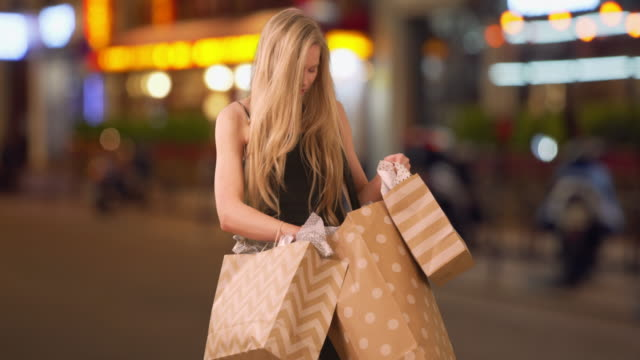 vídeos de stock, filmes e b-roll de attractive caucasian female consumer out on shopping spree in city - viciado em compras