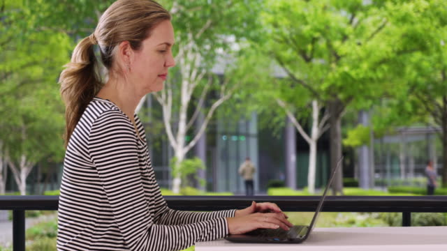 attractive caucasian woman answering work emails outside - weibliche angestellte stock-videos und b-roll-filmmaterial