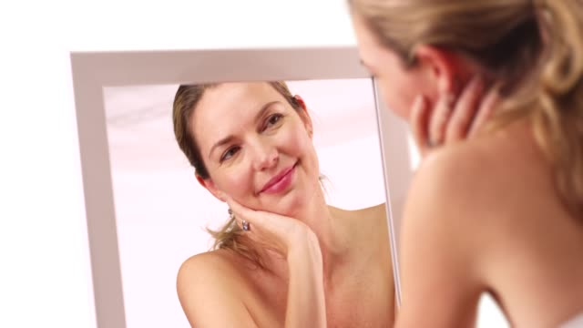 attractive caucasian woman smiling at reflection in mirror on white background - vanity stock videos & royalty-free footage