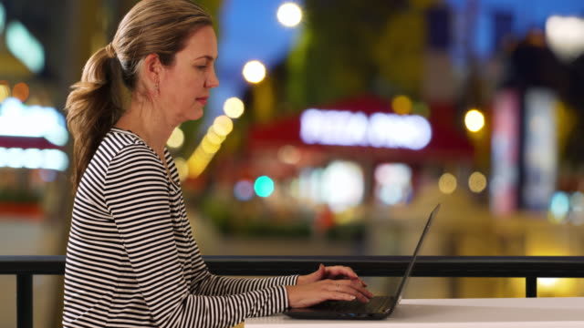 attractive caucasian woman typing on laptop outside at night - weibliche angestellte stock-videos und b-roll-filmmaterial