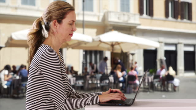 attractive caucasian woman typing on laptop outside - weibliche angestellte stock-videos und b-roll-filmmaterial