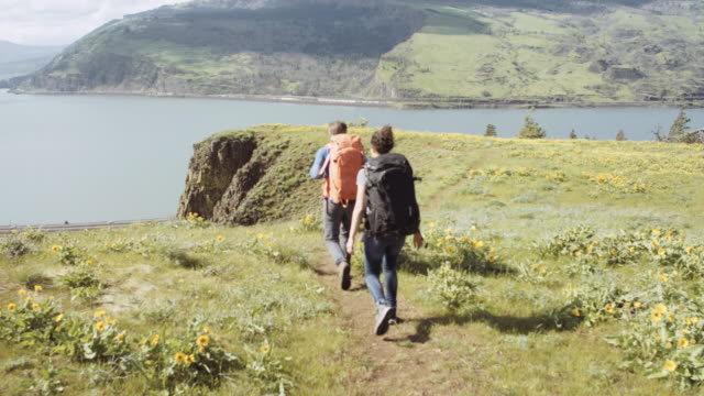 attractive couple backpacking along cliff edge - columbia river gorge stock videos & royalty-free footage