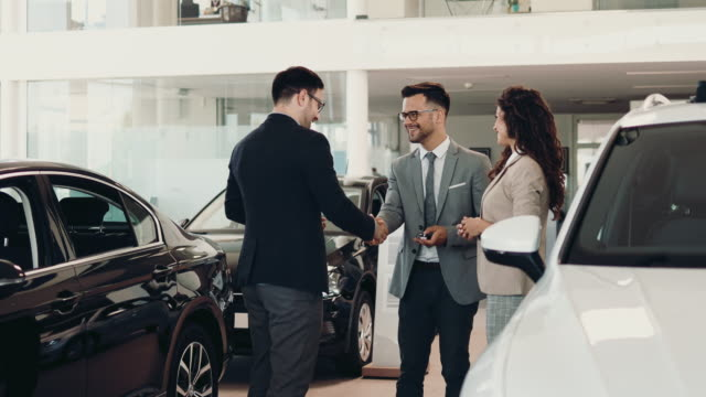 attractive couple buying new car - buying stock videos & royalty-free footage