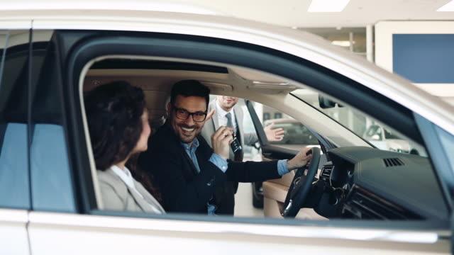 attraktives paar kauft neues auto - ehemann stock-videos und b-roll-filmmaterial
