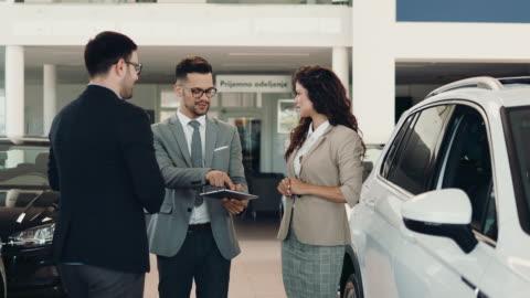 vidéos et rushes de couples attirants achetant la nouvelle voiture - vendeur
