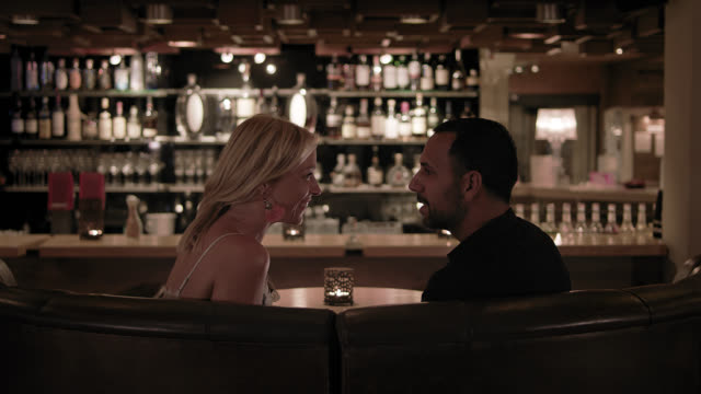 attractive couple converse in a hotel bar during night - blonde woman in her thirties and the dark haired man in foreground - the dimly but nice lit bar with good interior design out of focus in background