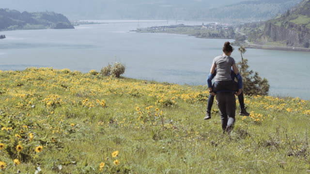 attractive couple piggy backing on a plateau overlooking a river - columbia river gorge stock videos & royalty-free footage