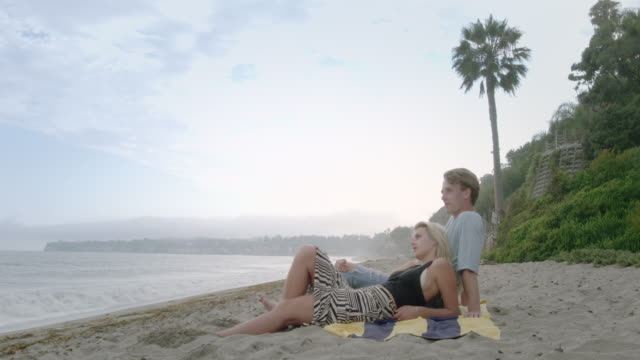 attractive couple sit on california beach watching waves on pacific ocean 4k - side lit stock videos & royalty-free footage