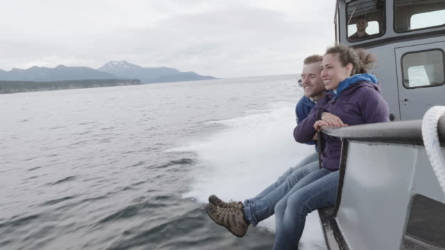 uhd 4k slomo: attractive couple sitting on a boat during a whale tour - whale watching stock videos and b-roll footage