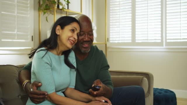 vidéos et rushes de couples attrayants regardant la télévision à la maison - 50 54 ans
