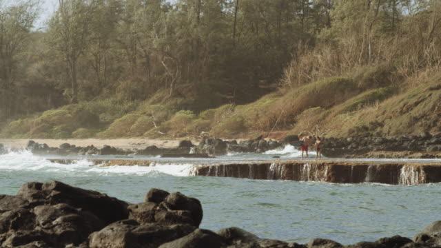 Aantrekkelijk koppel met surfplanken op een rots-richel