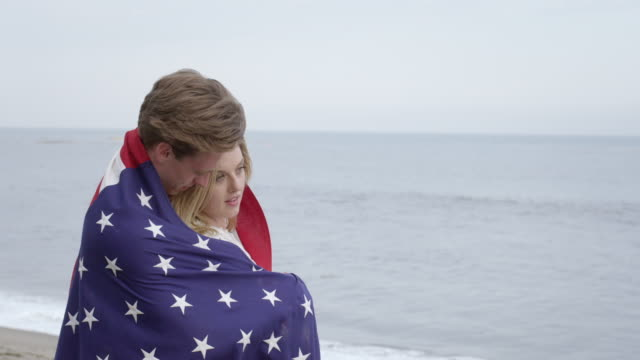 attractive couple wrap themselves in stars and stripes at the beach 4k - vesper stock stock videos & royalty-free footage