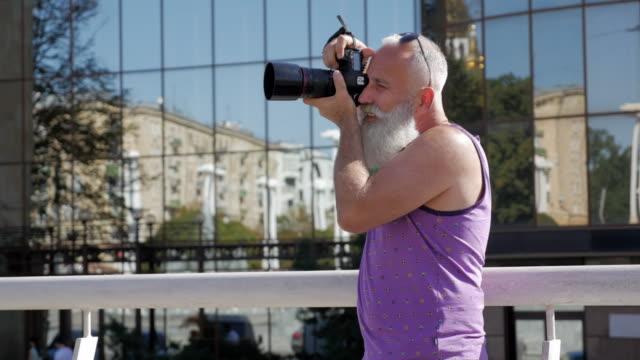 vídeos de stock, filmes e b-roll de homem idoso atraente fotografando com câmera - 50 59 years