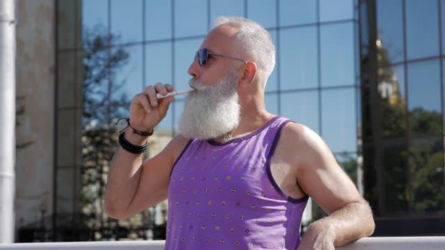 vídeos de stock, filmes e b-roll de o homem idoso atraente fuma cigarro eletrônico - 50 59 years