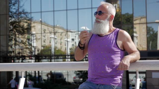魅力的な老人、電子タバコを吸う - 50 59 years点の映像素材/bロール