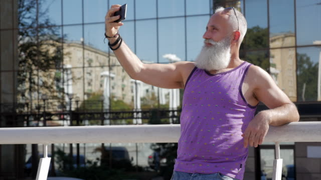魅力的な老人は、selfie のスマート フォンを使用してください。 - 50 59 years点の映像素材/bロール