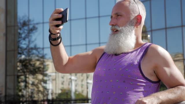 vídeos de stock, filmes e b-roll de o homem idoso atraente usa um smartphone para selfie - 50 59 years