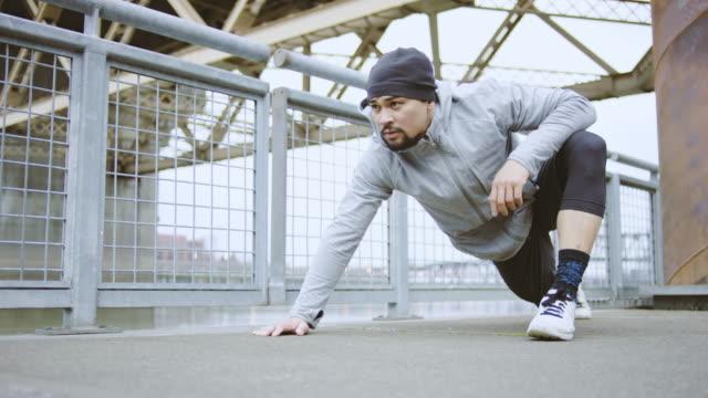 stockvideo's en b-roll-footage met aantrekkelijke etnische man uitoefening/stretching buitenshuis - fatcamera