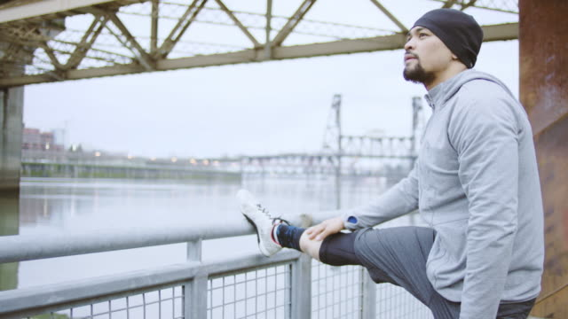 attractive ethnic male exercising/stretching outdoors - stretching stock videos and b-roll footage
