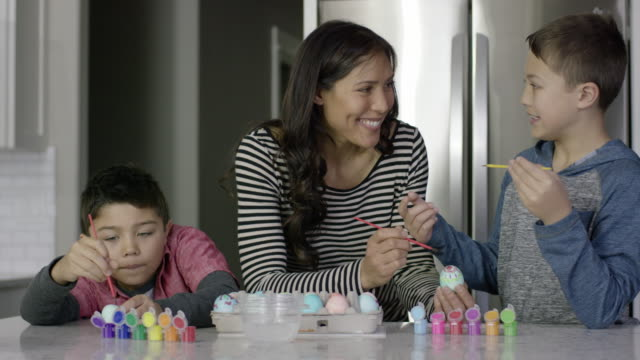 attractive ethnic mother painting easter eggs with her young sons - pacific islander family stock videos & royalty-free footage