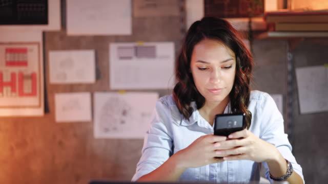 vidéos et rushes de architecte féminin attirant utilisant le téléphone portable dans le bureau - jeunes femmes