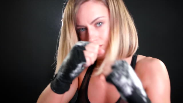 attractive female boxer punching with talcum powder flying around in 120fps slow motion - punching stock videos and b-roll footage
